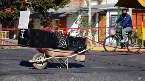 A coffin wrapped in plastic containing the body of an unidentified man, who died last week, sits on a wheelbarrow in the middle of a street in Cochabamba, Bolivia, July 4, 2020.