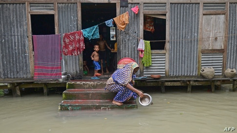 A woman washes her cooking pot in the flood waters outside her house in Sreenagar, Bangladesh.