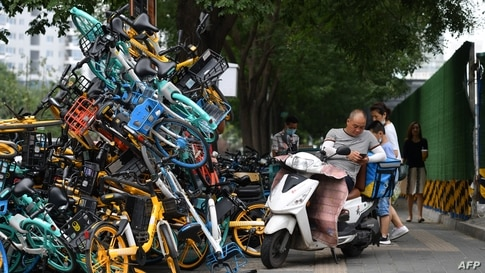 A delivery rider rests on a scooter next to a stack of shared bicycles on a sidewalk in Beijing, China.