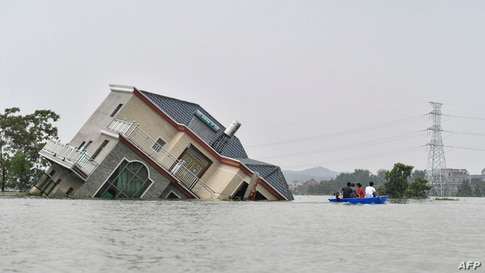 Residents ride a boat past a damaged house near the Poyang Lake due to torrential rains in Poyang county, Shangrao city in China's central Jiangxi province, July 15, 2020.