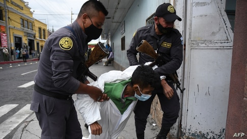 Penitentiary system guards carry an inmate with symptoms related to the novel coronavirus at the COVID-19 unit of San Juan de Dios hospital in Guatemala City, July 13, 2020.