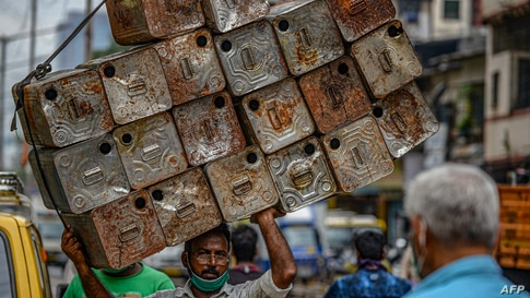 A laborer carries a load of empty oil tins in Dharavi in Mumbai, India.