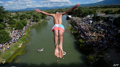 """A diver jumps from the 22-meter-high bridge """"Ura e Shenjte"""" near the town of Gjakova, Kosovo, as a sign of protest after police canceled the 70th traditional annual High Diving competition."""