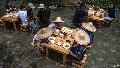 Customers eat lunch at a restaurant with tables in a stream of a river in Kampung Kemensah on the outskirts of Kuala Lumpur on July 14, 2020. (Photo by Mohd RASFAN / AFP)