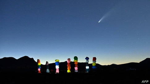 """Comet NEOWISE or C/2020 F3 is seen in the sky, above the """"Seven Magic Mountains"""" art installation by artist Ugo Rondinone, in Jean, Nevada, July 15, 2020."""