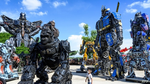 """A child looks at a figure of King Kong in front of life-sized sculptures of characters from the """"Transformers"""" film franchise, all made of scrap metal parts, at the Ban Hun Lek museum in Ang Thong, some 100km north of Bangkok, Thailand, July 18, 2020."""