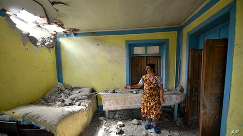 A local woman shows damage in her house after the shelling by Armenian forces in the Tovuz region of Azerbaijan.