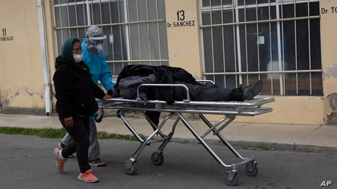 A healthcare worker dressed in protective gear pushes the body of a man, who died of COVID-19, on a stretcher outside the General Hospital in La Paz, Bolivia.