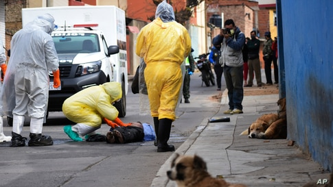 Health workers recover the body of a street vendor who was found dead at dawn by his neighbors in the Cerro San Miguel neighborhood of Cochabamba, Bolivia, July 25, 2020.