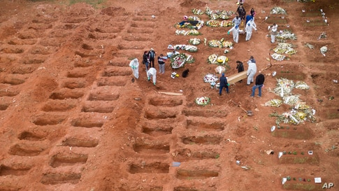 Cemetery workers in protective clothing bury three victims of the new coronavirus at the Vila Formosa cemetery in Sao Paulo, Brazil.