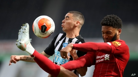 Liverpool's Joe Gomez, right, challenges Newcastle's Miguel Almiron during the English Premier League soccer match between Newcastle and Liverpool at St. James' Park in Newcastle, England.