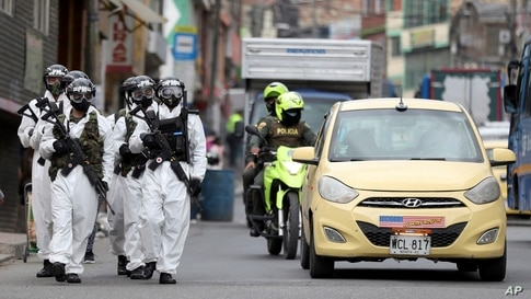 Soldiers in protective gear patrol Ciudad Bolivar, a neighborhood with high cases of the new coronavirus in Bogota, Colombia, July 13, 2020.