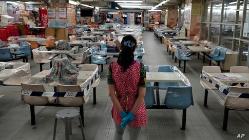 A restaurant employee looks at empty tables at a Chinese food court in Hong Kong.