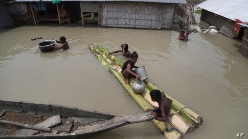 Flood affected villagers are seen near their partially submerged houses in Gagolmari village, Morigaon district, Assam, India.