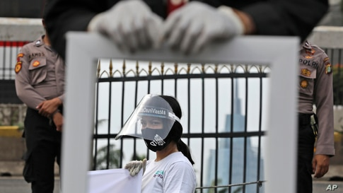 A mirror reflects an activist wearing a mask and protective face shield as a precaution against the new coronavirus outbreak during a small protest outside the parliament in Jakarta, Indonesia.