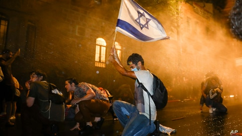 Israeli police use a water cannon to disperse demonstrators during a protest against Prime Minister Benjamin Netanyahu in Jerusalem, July 18, 2020.
