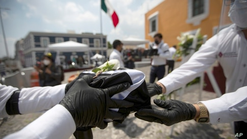 State workers handle an urn holding ashes of a Mexican, who died in the U.S. from COVID-19 complications, during a ceremony in Puebla, Mexico, July 13, 2020.