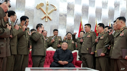"""North Korean leader Kim Jong Un, sitting center, is surrounded by senior military officials holding """"Paektusan"""" commemorative pistols they received from him during a ceremony in Pyongyang, July 26, 2020."""