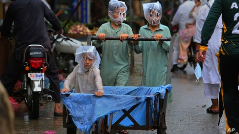Boys cover their faces with plastic bags while pushing a handcart during rainfall in Peshawar, Pakistan.