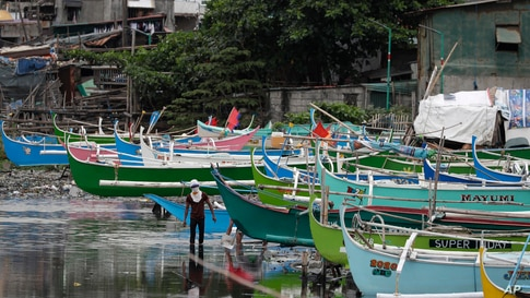 A man walks by docked fishing boats during the start of a lockdown due to a rise in COVID cases in the city of Navotas, Manila, Philippines.