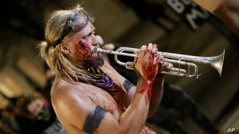 A bloodied demonstrator plays a trumpet after clashing with police during a Black Lives Matter protest at the Mark O. Hatfield United States Courthouse in Portland, Oregon.