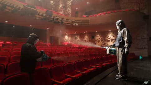 Workers wearing protective gears spray disinfectant as a precaution against a new coronavirus at a theater in Sejong Center in Seoul, South Korea.