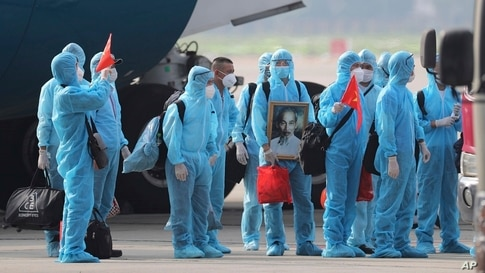Vietnamese COVID-19 patients, who were working in Equatorial Guinea, holding Vietnamese flags and carrying a portrait of the national leader Ho Chi Minh, arrive at the Noi Bai airport in Hanoi.