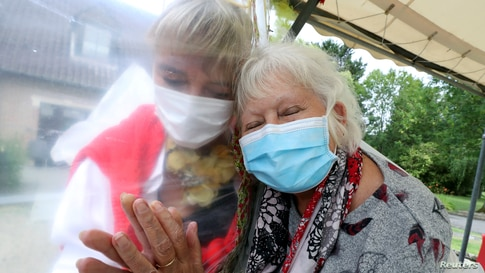 """Lily Hendrickx, 83, a resident at Belgian nursing home """"Le Jardin de Picardie"""" hugs Marie-Christine Desoer, the director of the residence, through a wall made with plastic sheets, in Peruwelz, July 1, 2020."""