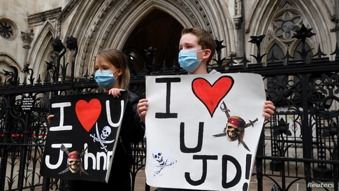 Fans of actor Johnny Depp hold placards as they wait for him to arrive at the High Court, in London, Britain.
