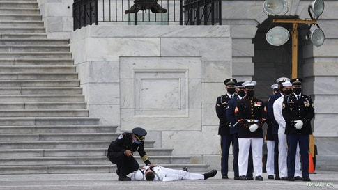 A member of a U.S. military honor guard is checked on after collapsing in the heat of the day as a hearse carrying the casket of civil rights pioneer and longtime U.S. Rep. John Lewis (D-GA) arrives at the U.S. Capitol in Washington.