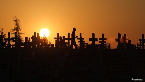 A man is silhouetted against sunset sky as he walks past the graves of soldiers killed in the 1974 Turkish invasion of Cyprus at the Tymvos Macedonitissas military cemetery in Nicosia, Cyprus, July 19, 2020.