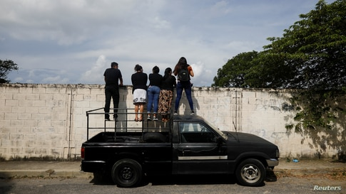 A family watches the funeral of a relativeat La Bermeja cemetery in San Salvador, El Salvador, under the coronavirus disease (COVID-19) protocols, as the outbreak continues, July 27, 2020.