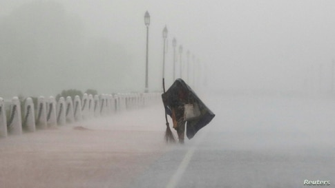 A woman covers herself with a plastic sheet as she walks during heavy rains in New Delhi, India.