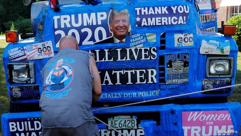 """A supporter of U.S. President Donald Trump ties off a banner hanging from a boom during Super Happy Fun America's """"Back the Blue/President Trump Standout"""" in Stoneham, Massachusetts, July 27, 2020."""