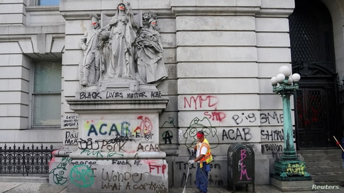 """A worker washes the sidewalk to remove graffitis after police dismantled the """"City Hall Autonomous Zone"""" that was in support of the Black Lives Matter movement in the Manhattan borough of New York City."""