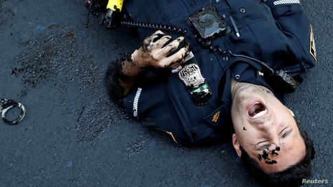 An officer from the New York Police Department is seen injured after attempting to detain a protester smearing paint on the Black Lives Matter mural outside of Trump Tower on Fifth Avenue in Manhattan, July 18, 2020.