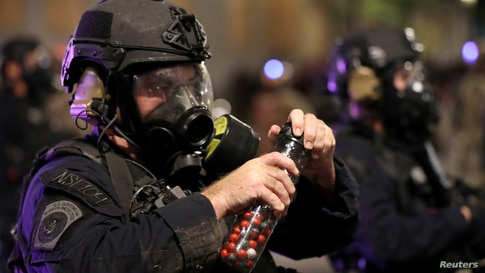 A federal law enfaA federal law enforcement officer holds pepper balls during a protest against racial inequality and police violence in Portland, Oregon, July 28, 2020.orcement officer holds pepper balls during a protest against racial inequality and police violence in Portland…