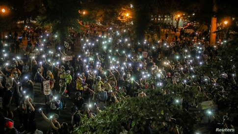People turn cellphone flashlights on during a demonstration against racial inequality and police violence in Portland, Oregon, July 29, 2020.