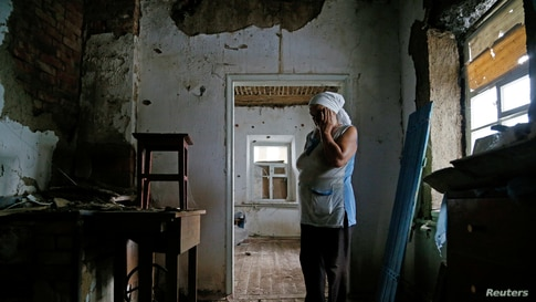Local resident Katerina Izvekova, 77, shows her house damaged during a military conflict between militants of the self-proclaimed Donetsk People's Republic and the Ukrainian armed forces in the rebel-controlled village of Vesele in Donetsk region.