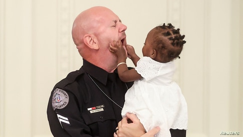 One-year-old Ryleigh Boyd grabs the face of Berekely County Sheriff's Deputy William Kimbro during a roundtable discussion on law enforcement hosted by U.S. President Donald Trump in the East Room of the White House in Washington, July 13, 2020.