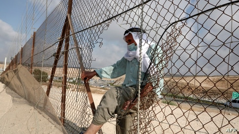 A Palestinian man enters illegally from a breach in a barrier fence into Israeli territory from the village of al-Dahriya,…