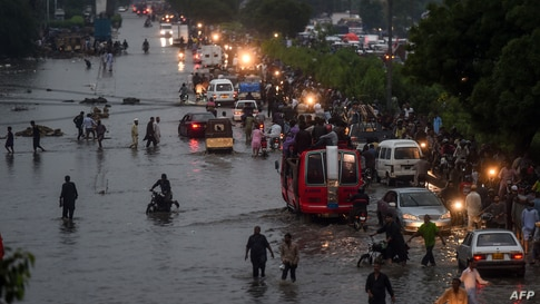 Motorists and pedestrians wade through a flooded street after heavy monsoon rains in the Pakistan's port city of Karachi on…