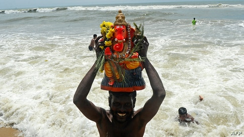 A volunteer carries a clay idol of Hindu elephant-headed deity Ganesh for immersion on the third day of the Ganesh Chaturthi…