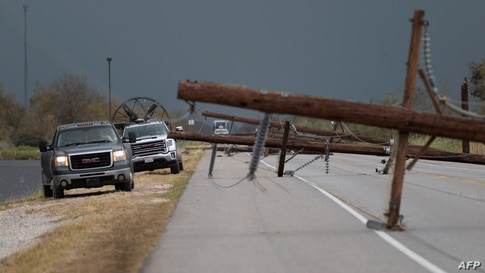 People trying to reach their homes in Cameron parish drive past downed power lines after the passing of Hurricane Laura south…
