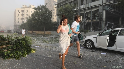 People run for cover following an explosion in Beirut's port area, Lebanon, Aug. 4, 2020.