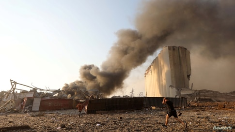 A man runs as smoke rises at the site of an explosion in Beirut, Lebanon, Aug. 4, 2020.