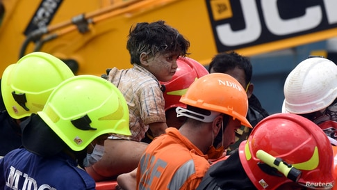 Rescue workers carry Mohammed Bangi, a four-year-old boy, after he was rescued from the rubble at the site of a collapsed five…