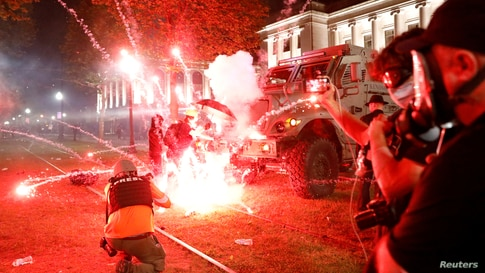 Flares go off in front of a Kenosha Country Sheriff Vehicle as demonstrators take part in a protest following the police…