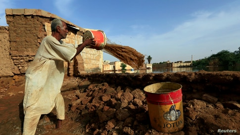 A resident pours out the waters of the Blue Nile floods within the Al-Ikmayr area of Omdurman in Khartoum, Sudan August 27,…