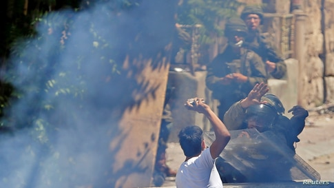 A Palestinian demonstrator hurls stones at Israeli soldiers during a protest in Hebron in the Israeli-occupied West Bank August…